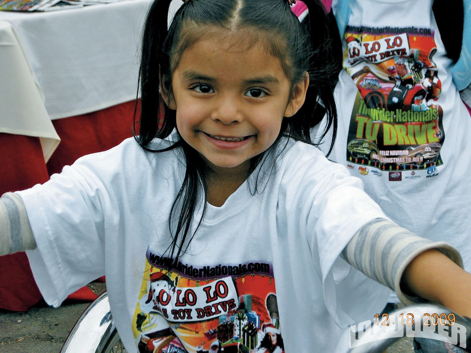 Josie the youngest of the Castro family, proudly rides her bike at the toy drive.