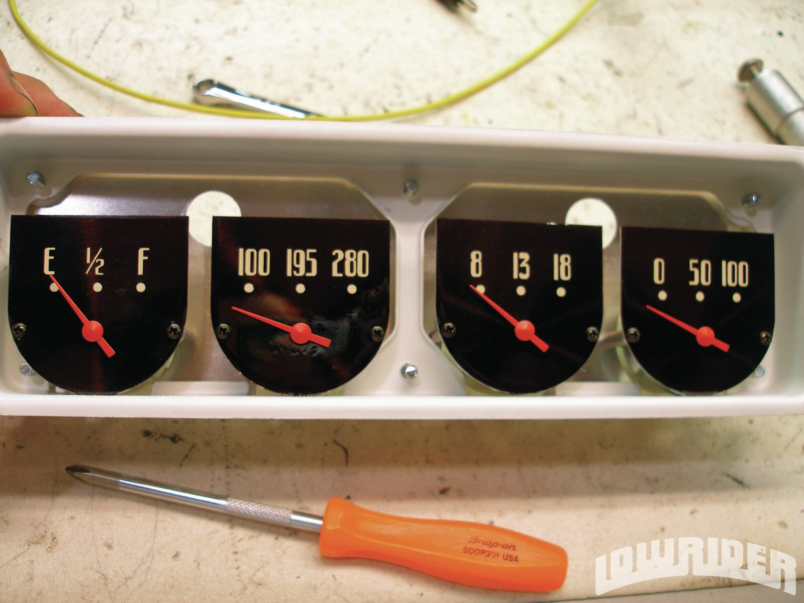 <strong>15</strong>. All four gauges mount to a single aluminum plate that is then installed into the modified stock housing. The gauge faces have been treated to the same—albeit less intricate—retrofit, graphically speaking.