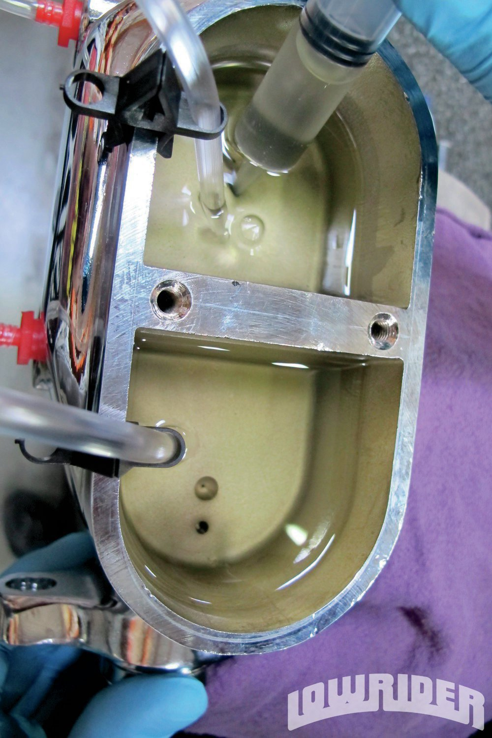 <strong>11</strong>. The syringe was put into the rear porthole of the cylinder and Rob started pushing the fluid through.