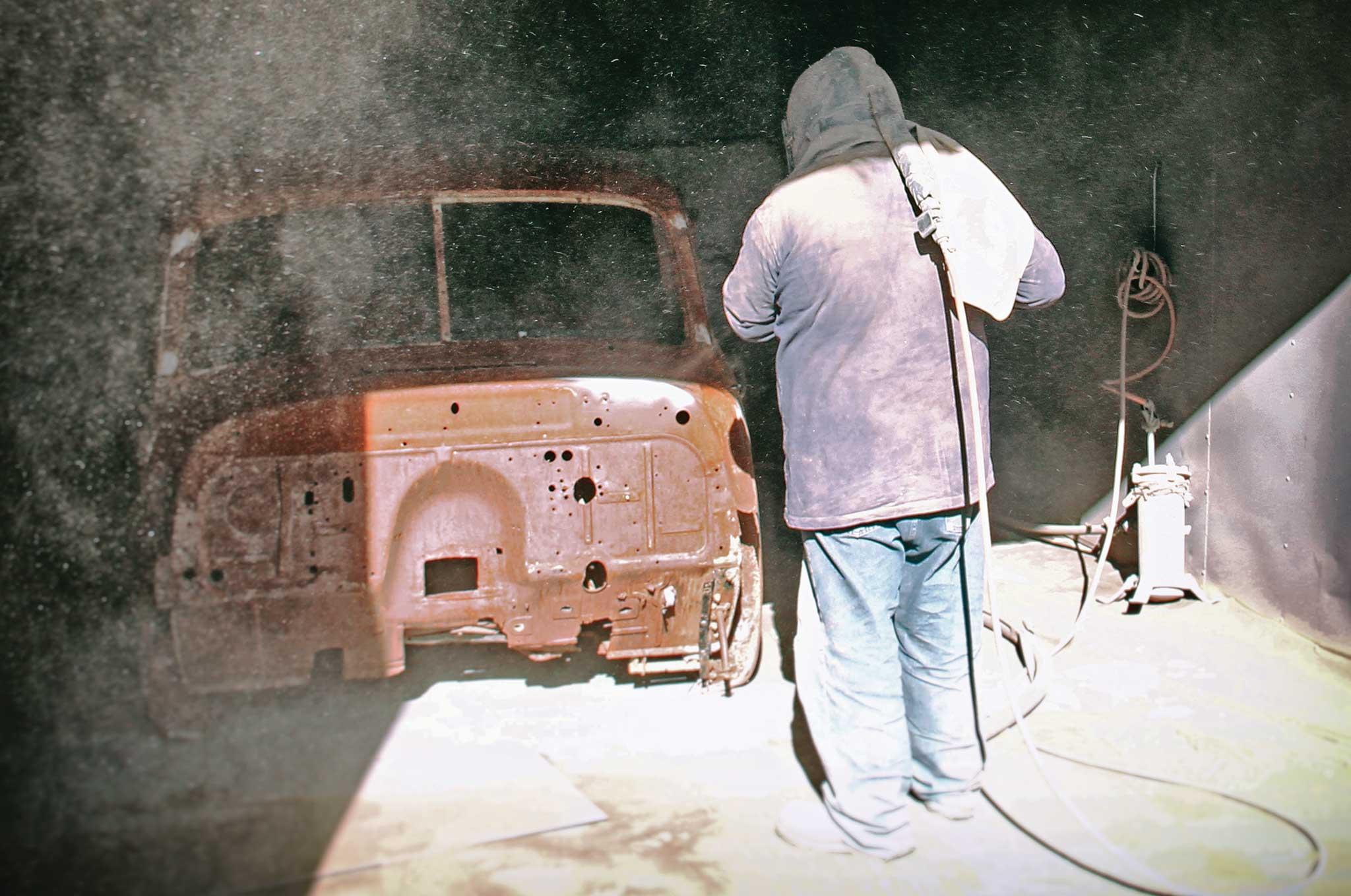 Worker sandblasting a truck cab.